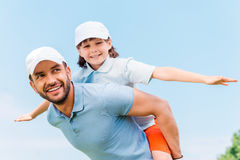 Having fun together. Cheerful young men carrying his son on shoulders while standing outdoors Stock Photography