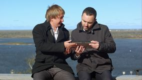 Having fun. Two man with tablet sitting on bench royalty free stock photo