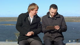 Having fun. Two man with tablet sitting on bench stock footage