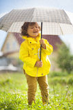 Having fun under the rain, emotional little girl. Cute toddler girl wearing yellow waterproof coat and boots with big adult umbrella having fun In the pouring royalty free stock image