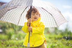 Having fun under the rain, toddler girl with umbrella. Cute toddler girl wearing yellow waterproof coat and boots with big adult umbrella having fun In the royalty free stock image
