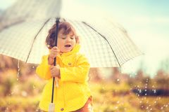 Having fun under the rain, toddler girl with umbrella. Cute toddler girl wearing yellow waterproof coat and boots with big adult umbrella having fun In the Stock Photos