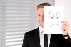 Having fun at work. Cheerful young businessman holding a poster Royalty Free Stock Photo