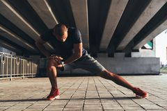 Having a good stretch. Handsome young African man in sports clothing stretching while warming up outdoors royalty free stock photography
