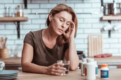 Blonde-haired woman having heartache spilling water on t-shirt. Having heartache. Blonde-haired depressed and stressed woman having heartache spilling water on t stock photo