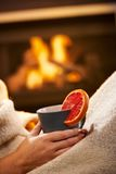Having hot tea in front of fireplace Royalty Free Stock Images