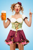 Having an idea. Young sexy Oktoberfest waitress wearing a traditional Bavarian dress dirndl holding a beer mug, and having an idea, on blue background Stock Images
