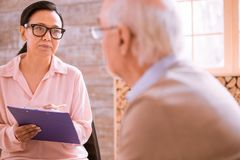 Pleased Asian woman working in retirement home stock images