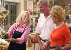 Having A Laugh With Customers. A female garden center manager establishing a good rapport with her customers.  Focus on eyes of store manager Stock Images