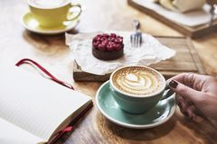 Having lunch with coffee flat white and sweet chocolate cookie in a cafe or restaurant. Woman hand holds a green cup. Blank notebook spread layout royalty free stock photo