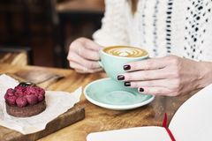 Cup of coffee latte on wooden table or background in woman hands from above. Having lunch in cafe. Opened notebook Stock Photo