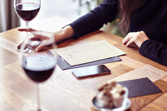 Having lunch with glasses red wine in a cafe. Friends meeting indoor. Hipster paper envelope Royalty Free Stock Image