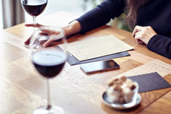 Having lunch with red wine in a cafe. Friends meeting indoor. Hipster paper envelope.  royalty free stock photos