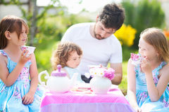 Having many children father paying game with daughters Stock Photo