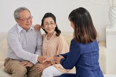 Having Meeting with Insurance Agent. Back view of friendly insurance agent greeting senior clients with handshake while having meeting at cozy office Royalty Free Stock Photos