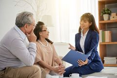 Having Meeting with Professional Estate Agent. Attractive Asian estate agent with charming smile showing senior couple photos of apartments offered for sale Royalty Free Stock Photography