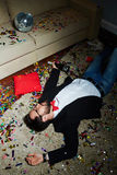 Having nap after wild party. Intoxicated bearded man with bow tie having nap on carpet covered with confetti after wild house party Royalty Free Stock Image