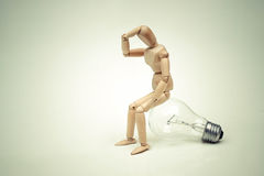Having no idea. Wood Figure Mannequin sitting on an incandescent light bulb / Being stupid / Having no idea Stock Photography