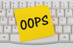 Having problems with your computer. A close-up of a keyboard with yellow sticky note with text Oops Stock Photo
