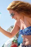 Having refreshed yourself in a hot day. A happy red-hair girll is laughing having refreshed herself pouring some water on from a bottle, Sunny beach, Bulgaria stock photo