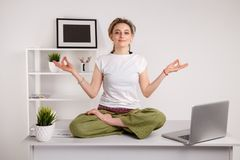 Having a rest in office. Yoga at work. Typing on the laptop and doing lotus pose. stock images