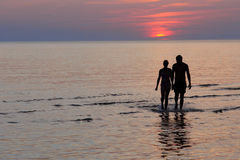 Having rest on the sea at sunset. Silhouette of a couple going swimming to the sea; sunset Stock Photography