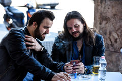 Having a smoke with a beer checking out something on the internet. Lighting a cigarette and looking something on the phone. Two male friends are having a smoke Royalty Free Stock Image