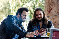 Having a smoke with a beer checking out something on the internet. Lighting a cigarette and looking something on the phone. Two male friends are having a smoke Royalty Free Stock Images