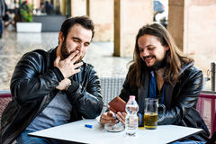 Having a smoke with a beer checking out something on the internet. Lighting a cigarette and looking something on the phone. Two male friends are having a smoke Royalty Free Stock Photography