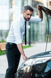Having some car troubles. Serious young businessman looking inside of the vehicle hood while standing near his car Stock Photo