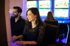 Having some fun in a casino. Cute young women sitting in a slot machine in a casino and having a good time royalty free stock photography