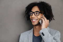 Having some great news!. Cheerful young African man talking on mobile phone and smiling while standing against grey background stock photos