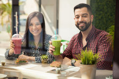 Having some healthy drinks. Happy young couple enjoying their healthy smoothies and sandwiches during lunch Stock Image