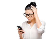 Having some problems. Beautiful young black hair woman holding mobile phone and looking at it while standing against white background Stock Photos