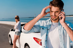 Having some road troubles. Frustrated young men talking on the mobile phone while his girlfriend leaning at their white convertible in the background Stock Photo