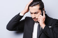 Having some troubles. Frustrated young businessman talking on the mobile phone and touching his head while standing against grey background Stock Photos