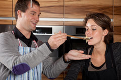 Having a taste. Man holding up the spoon to his girlfriend so she can taste Royalty Free Stock Photography