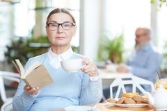Having tea and reading. Elegant women in eyeglasses and smart casual reading book while having tea with cookies in cafe Royalty Free Stock Photo