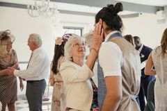 Having a Word with her Grandson on his Wedding day. Senior women is appreciating her grandson on his wedding day. She is dancing and talking to him with her Royalty Free Stock Images