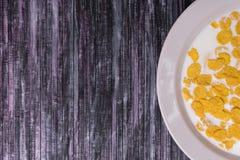 havreflakes mjölkar Platta på en träbakgrund Vit maträtt med flingor Gulingflingor Bärgningen är en avfalls Royaltyfri Fotografi
