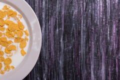 havreflakes mjölkar Platta på en träbakgrund Vit maträtt med flingor Gulingflingor Bärgningen är en avfalls Royaltyfria Bilder