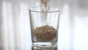 Havreflingor häller in i ett genomskinligt tomt exponeringsglas Hällande gryn in i ett klart exponeringsglas stock video