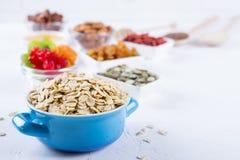 Havreflingor i blått bowlar och olika läckra ingredienser för sund frukost på köksbordet arkivfoton