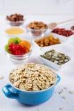 Havreflingor i blått bowlar och olika läckra ingredienser för sund frukost på köksbordet royaltyfri foto