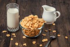 Havreflingor med mjölkar tillbringaren och exponeringsglas på trätabellen arkivfoto