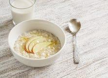 Havregröt med äpplet och honung i en vit bunke och ett exponeringsglas av naturlig yoghurt Arkivbild