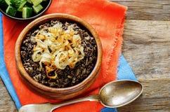 Havregröt som göras med lösa ris och svarta linser med stekte lökar Arkivfoto