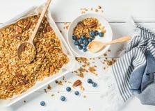 Havregranola med det pecannötmuttrar, yoghurt och blåbäret i bunke arkivfoto