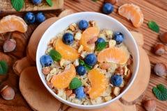 Havrehavregröt med bär och muttrar Hemlagad havregröt med den nya tangerin, blåbär, hasselnötter och mintkaramellen i en vit bunk Fotografering för Bildbyråer
