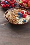 Havremjöl, granola, muttrar och bär i bunkar på träbakgrund Arkivbild